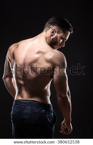 attractive bodybuilder sportsman shows perfect body muscles on black background; fitness man; bodybuilding and gym sport; athlete guy;