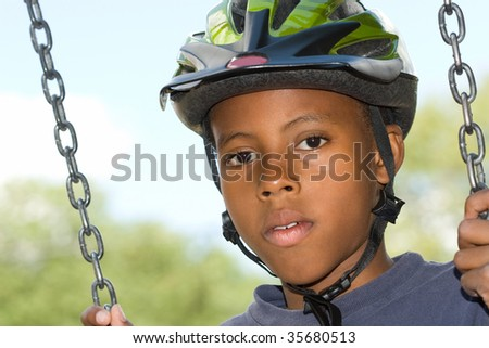 attractive boy swinging while wearing a bicycle helmet in the summertime - stock photo