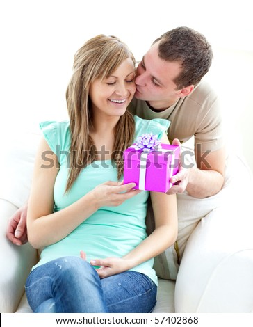 Attractive boyfriend giving a present and a kiss to his glowing girlfriend against white background
