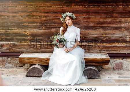 Attractive bride in a beautiful dress sitting in the waiting groom. Outdoor - stock photo