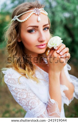 Attractive bride  with stylish  hairstyle posing in the garden in her wedding day. Holding in arms tender  balmy white rose flower. - stock photo