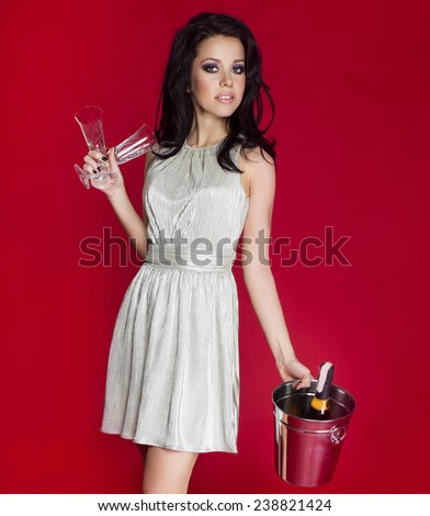 Attractive brunette beautiful woman posing with champagne glasses, celebrating. Red background. - stock photo