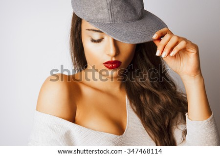 Attractive brunette beauty with long hair and red lips wear hat and looking down. Fashion and make up style. Toned in warm colors. Studio shot, horizontal. - stock photo