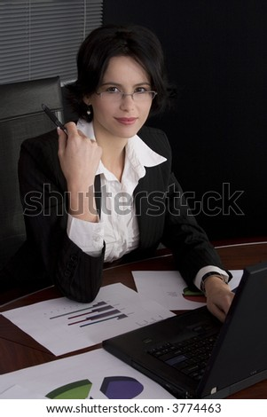 Attractive brunette business woman working at her desk