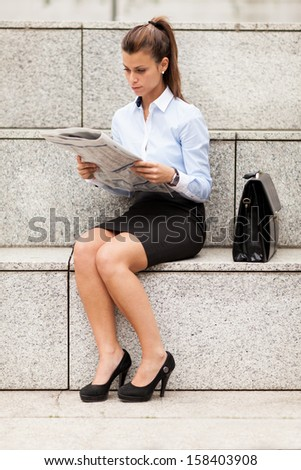 Attractive brunette businesswoman is reading the newspaper - stock photo