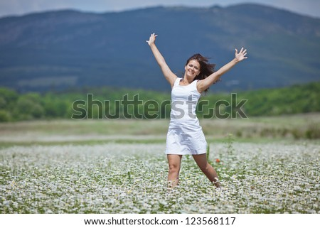 Attractive brunette crosses chamomile meadow. Girl in chamomile field