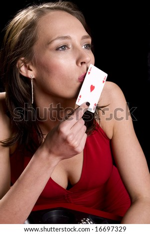 Attractive brunette dressed in a red dress kissing the ace of hearts