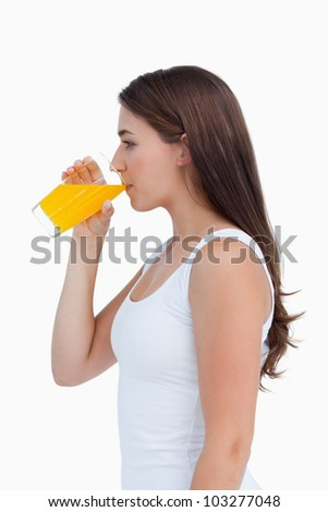 Attractive brunette drinking an orange juice against a white background - stock photo