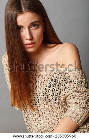 attractive brunette fashion model woman sitting over gray background - stock photo