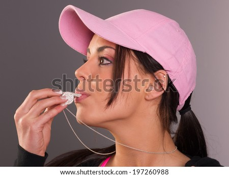 Attractive Brunette Female Blows Whistle Pink Ball Cap Whistleblower - stock photo