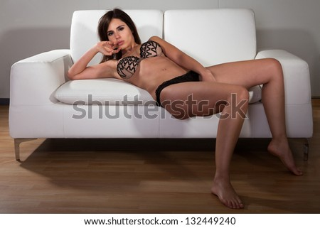Attractive Brunette Female In Lingerie Sitting On A Couch