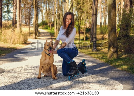 Attractive brunette female posing with her dog on a road in a spring nature par. - stock photo