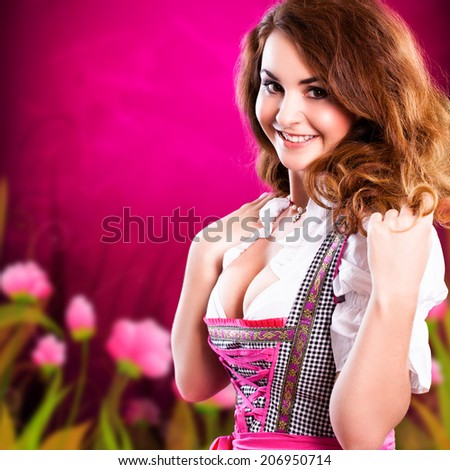 attractive brunette girl in a dirndl inf front of a spring background  - stock photo