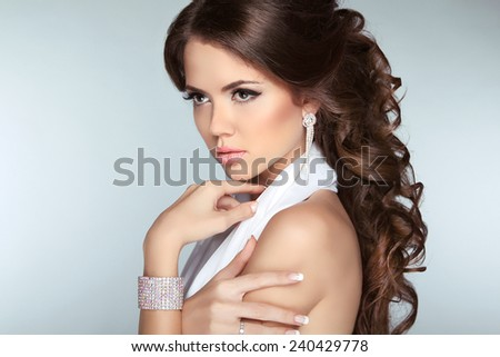 Attractive brunette girl model with long wavy hair styling, makeup and fashion jewelry isolated on gray background