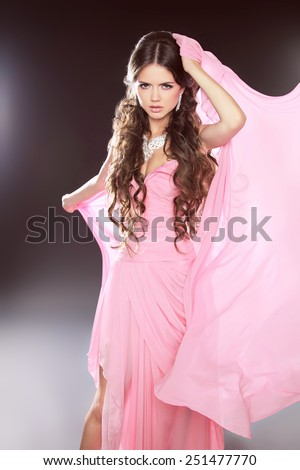 Attractive brunette girl wearing in pink dress with blowing chiffon. Long wavy hair styling. Studio photo. - stock photo