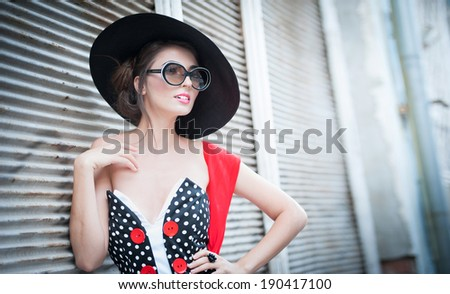 Attractive brunette girl with black hat, red scarf and sunglasses posing outdoor. Beautiful fashionable young woman with modern accessories, urban shot. Gorgeous brunette with large black hat smiling. - stock photo