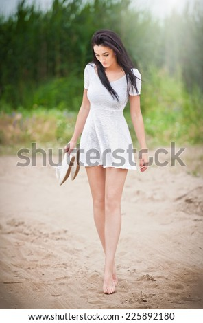 Attractive brunette girl with short white dress strolling barefoot on the countryside road. Young beautiful woman walking with shoes in hand with forest in background. Female with long legs outdoor - stock photo