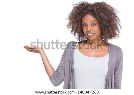 Attractive brunette holding hand out as a presentation on white background - stock photo
