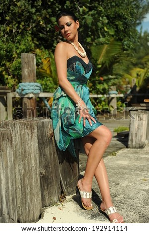 Attractive brunette in fashion dress standing in front of palm tree - stock photo