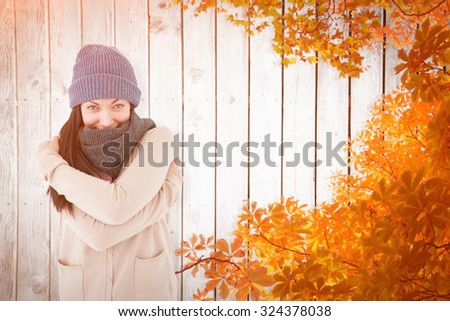 Attractive brunette looking at camera wearing warm clothes against autumn leaves on wood - stock photo
