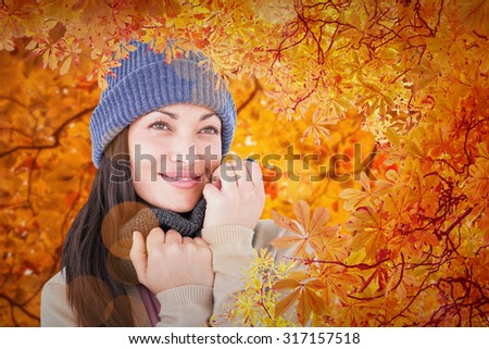 Attractive brunette looking up wearing warm clothes against autumn scene - stock photo