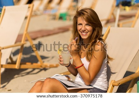Attractive brunette lying on a sunbed on a beach, drinking lemonade, reading a magazine and enjoying the sun - stock photo