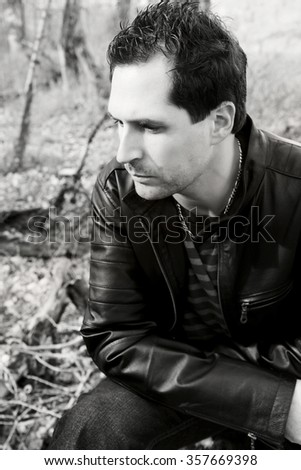 Attractive brunette male model outdoors during fall months - stock photo