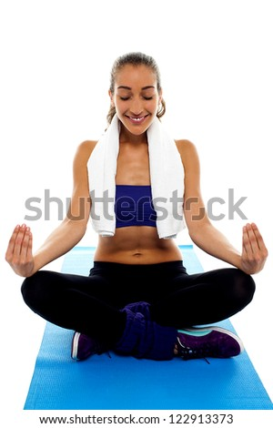 Attractive brunette meditating in lotus posture, sitting on blue mat.