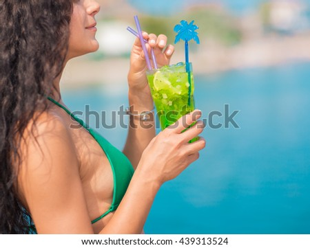 Attractive brunette on the beach. Young woman in swimwear drinking cocktail on the beach - stock photo