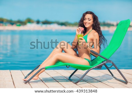 Attractive brunette on the beach. Young woman in swimwear drinking cocktail on the beach