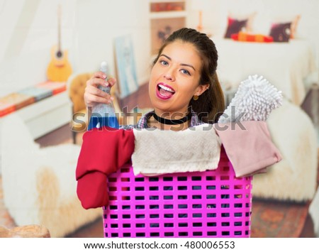 Attractive brunette peeking out head from behind pink plastic laundry basket, holding spray bottle containing blue cleaning liquid, smiling and posing for camera, messy apartment background