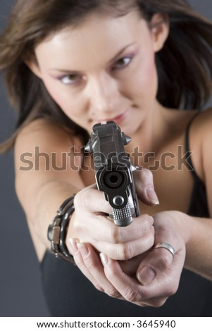 Attractive brunette pointing handgun towards camera