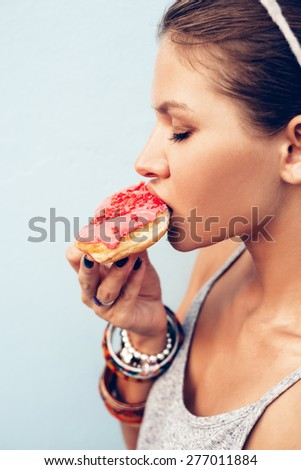 Attractive brunette sexy woman eating tasty donut. Close-up portrait - stock photo