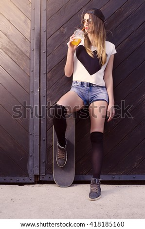 Attractive brunette skater girl posing on wooden door while drinking juice with straw  - stock photo