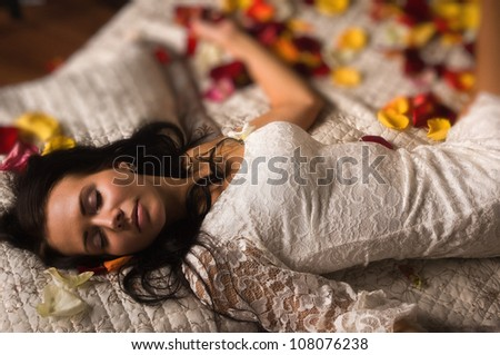 Attractive brunette sleeping on a bed in a boudoir