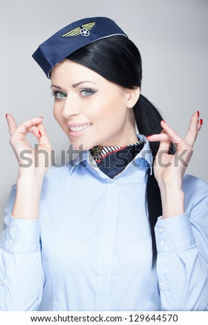 Attractive brunette stewardess in blue button down shirt in studio