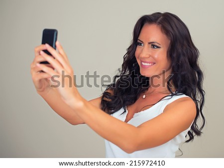 Attractive brunette taking selfie with cellphone. - stock photo