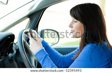 Attractive brunette teen girl using a mobile phone while driving - stock photo