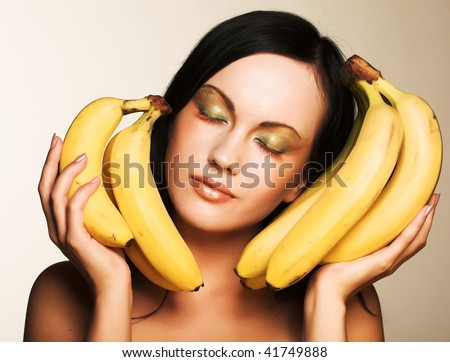 Attractive brunette with bananas on a white background - stock photo