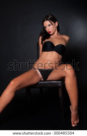 Attractive brunette with thong and bra posing on chair - stock photo