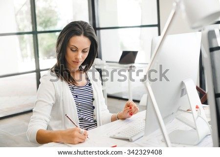 Attractive brunette woman at office desk work on computer - stock photo
