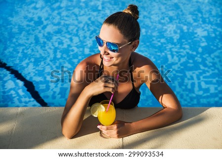 Attractive brunette woman drinking cocktail in the swimming pool - stock photo