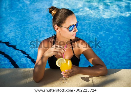 Attractive brunette woman drinking cocktail in the swimming pool. Girl looking away from the camera. - stock photo