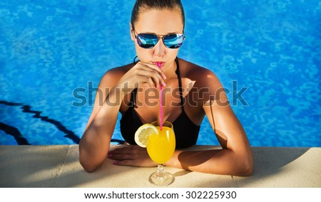 Attractive brunette woman drinking cocktail in the swimming pool. Girl looking straight at the camera.  - stock photo