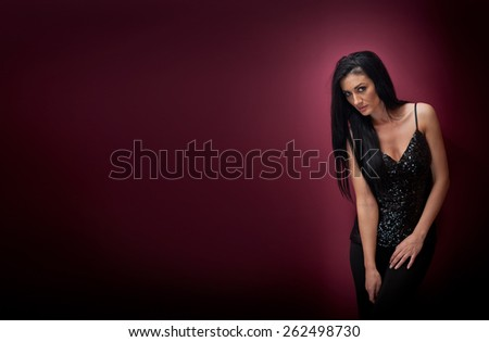 Attractive brunette woman in a black posing dramatic on purple background. Long hair female art portrait, studio shot. Genuine natural dark hair girl with sad look. Slim young woman posing indoor - stock photo