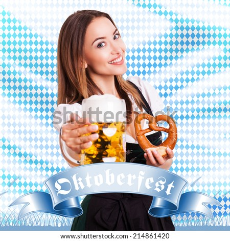 attractive brunette woman in a dirndl with beer and pretzel - stock photo