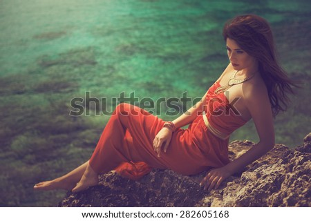 attractive brunette woman in a red dress sitting on the rocks - stock photo