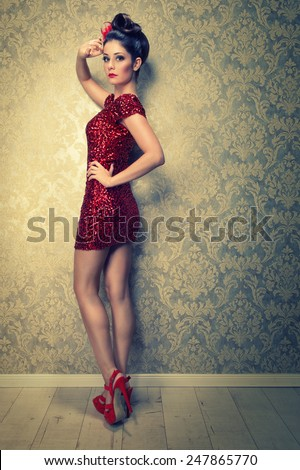 attractive brunette woman in a short red sequined cocktail dress - stock photo