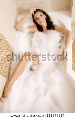 Attractive brunette woman in bath relaxing. Closeup of young woman in bathtub bathing - stock photo
