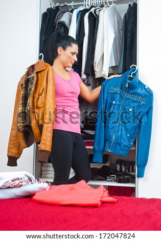 attractive brunette woman in front of closet full of clothes - stock photo
